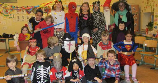 Die Schulklasse hat sich zu Fasching verkleidet und feiert im Klassenraum mit der Lehrerin