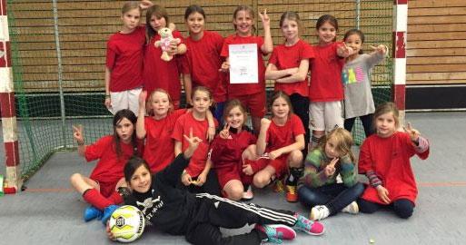 Schülerinnen einer Klassenstufe stehen und liegen vor einem Fußballtor in einer Turnhalle und halten stolz eine Urkunde in die Kamera