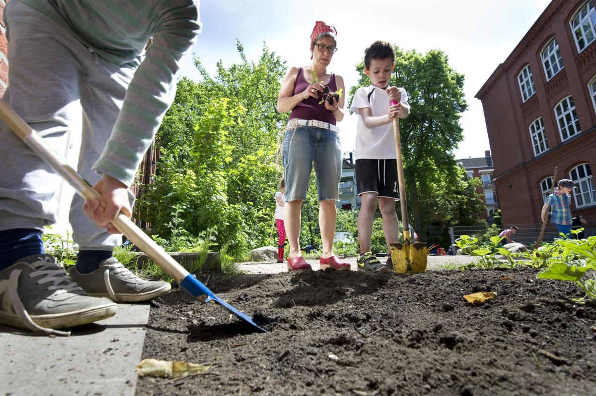 Zwei Schüler garben ein Beet mit frischer Muttererde um und wollen etwas pflanzen. Eine Betreuerin hilft den Kindern.