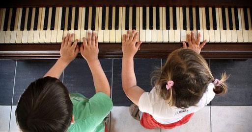 Jedem Kind ein Instrument ist das Motto der Schule Rothestraße. Zwei kleiner Kinder sitzen an einem Klavier und berühren die Tasten.