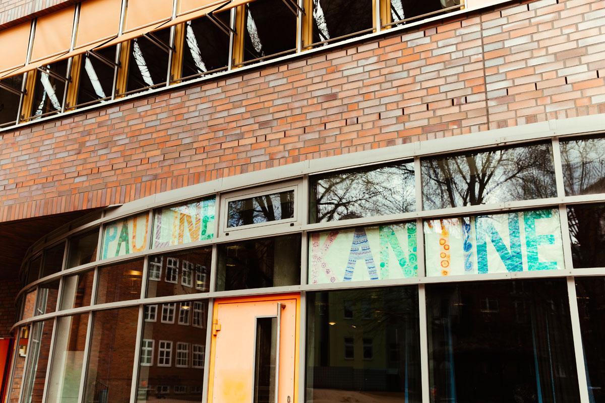 Das ist die Pauline Kantine der Schule mit vielen großen quadratischen Fenstern in dem der Schriftzug Pauline Kantine ganz bunt von Kindern gestaltet wurde