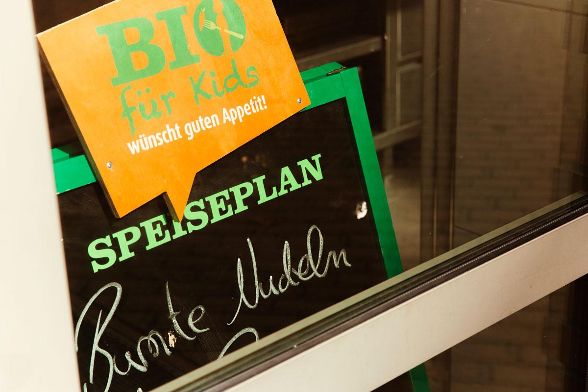 """In der Pauline Kantine sieht man durch die Fensterscheibe eine schwarze kleine Schultafel. Dort steht: Bio für Kids wünscht guten Appetit! Heute gibt es """"Bunte Nudeln""""."""