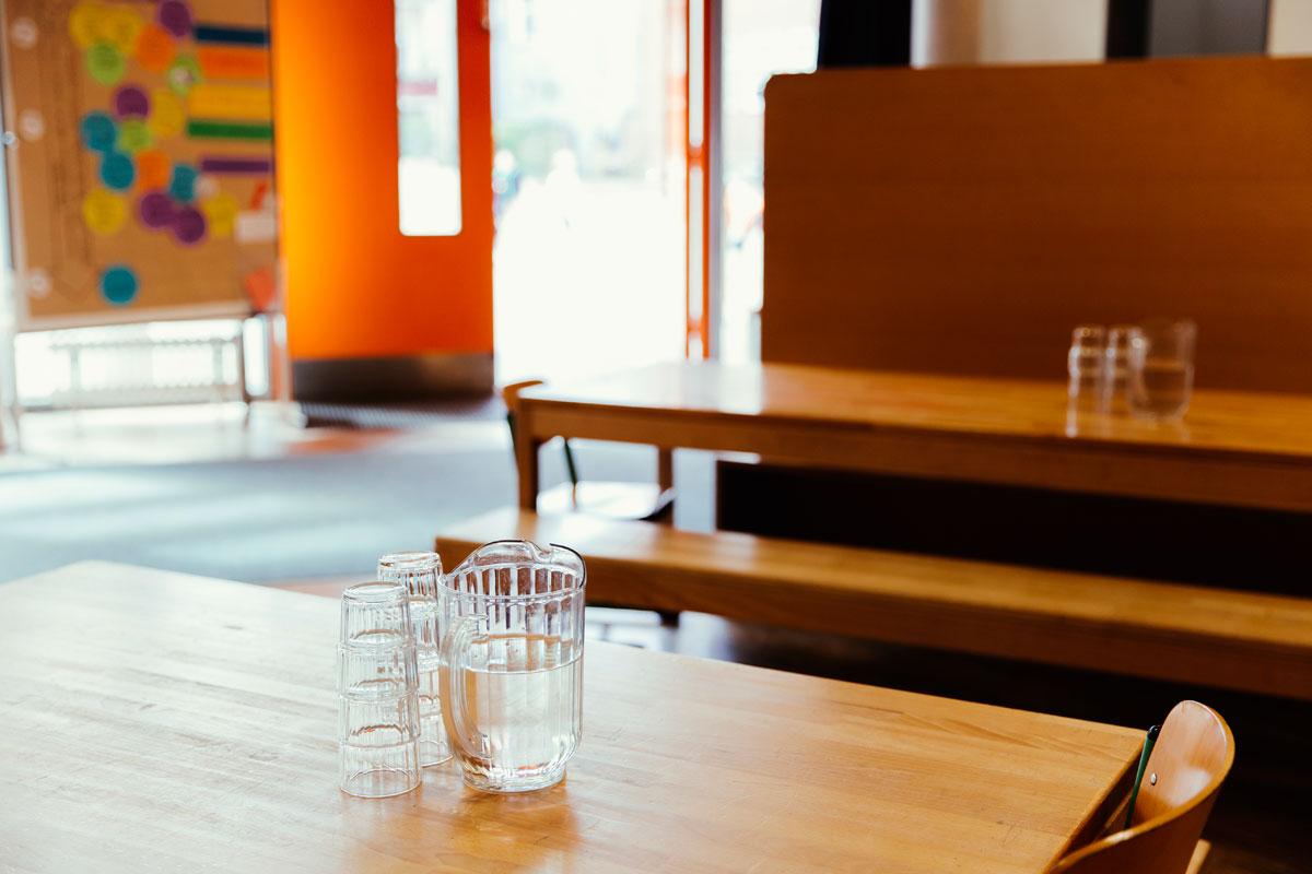 In der Pauline Kantine, der Mensa der Schüler stehen Holztische mit Holzbänken und Stühlen. Auf allen Tischen steht eine gefüllte Karaffe mit Wasser, dazu je 4 Gläser