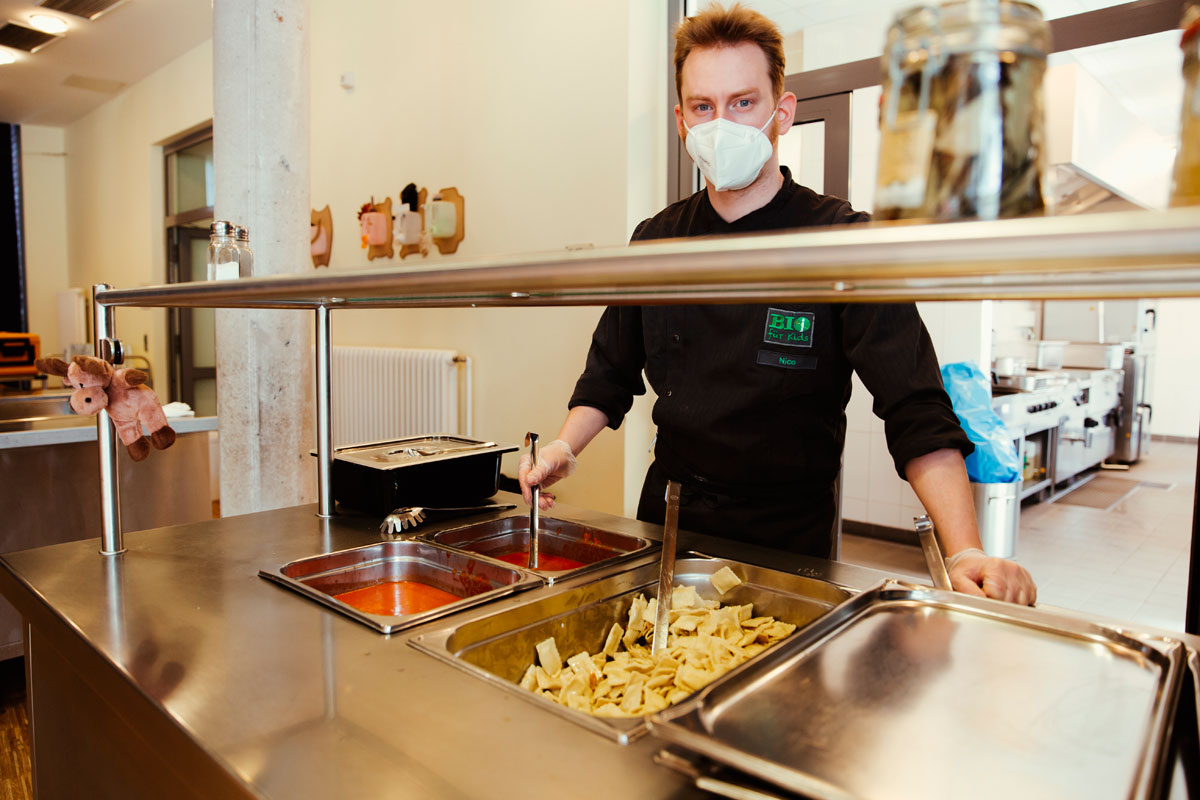 Das ist die Essensausgabe der Pauline Kantine. Nico, der Koch, hat einen Mundschutz auf und Handschuhe an. Heute gibt es Ravioli mit Tomatensauce