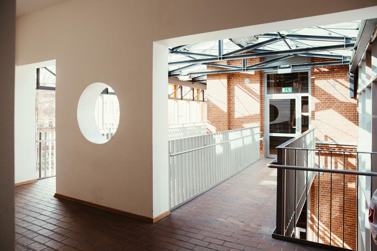 Das ist der Schulflur mit vielen Übergängen. Er sit lichtdurchflutet durch große Fenster und einem Glasdach.