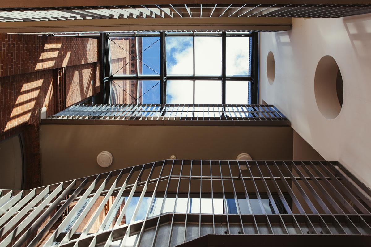 Das ist der Schulflur von unten nach oben fotografiert. Ganz oben sieht man über dem Treppengeländer große Fenster als Dach und der Himmel darüber ist blau.