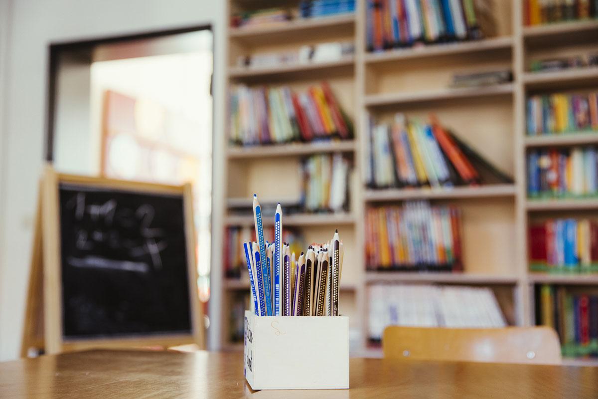 Viele Buntsifte stehen in einem Stifteständer auf einem Schreibtisch
