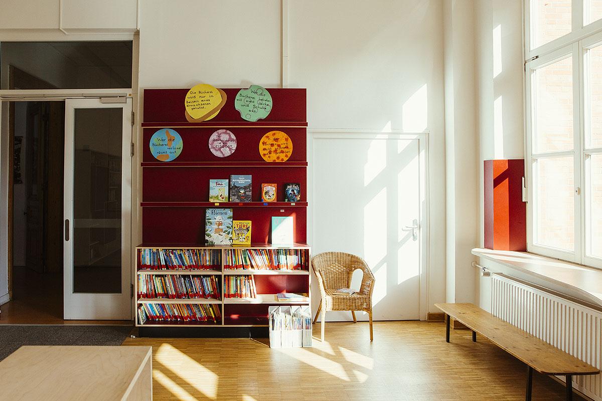 Das ist die Bücherei der Schule. Dort sieht man ein rotes Bücherregal, rechts daneben einen gemütlichen Korbsessel. Es scheint die Sonne aus den großen Fenstern herein.