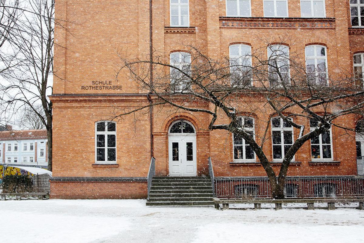 Hier sieht man im Winterden Eingang der Schule Rothestraße. Es schneit und viele Flocken wirbeln durcheinander.