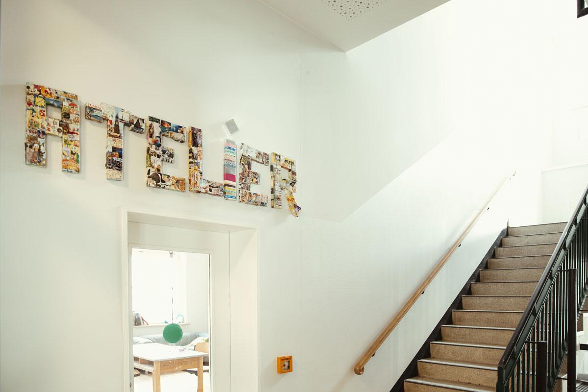 Das ist der Eingang zum Atelier aus dem Schulflur raus. Über der Tür steht in großem bunten Buchstaben: Atelier