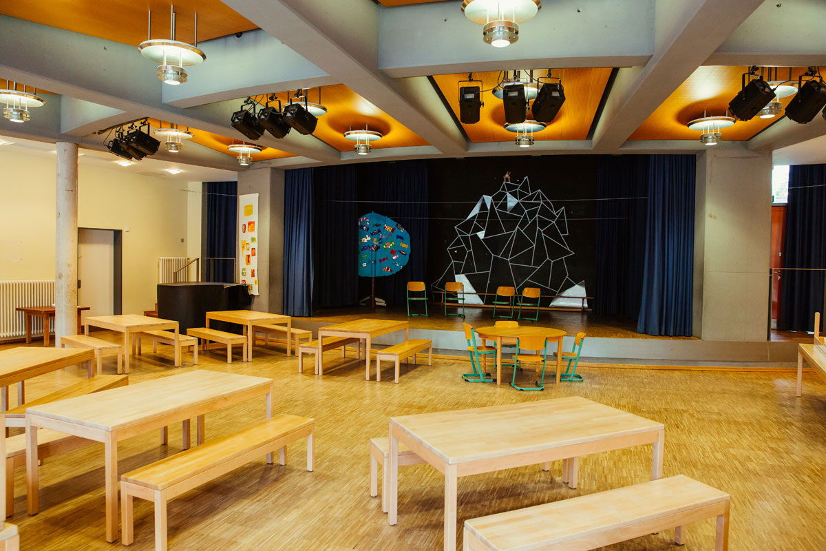 Das ist die Mensa mit vielen Holztischen und Bänken. Dahinter befindet sich eine Bühne mit dunkelblauen Vorhängen.
