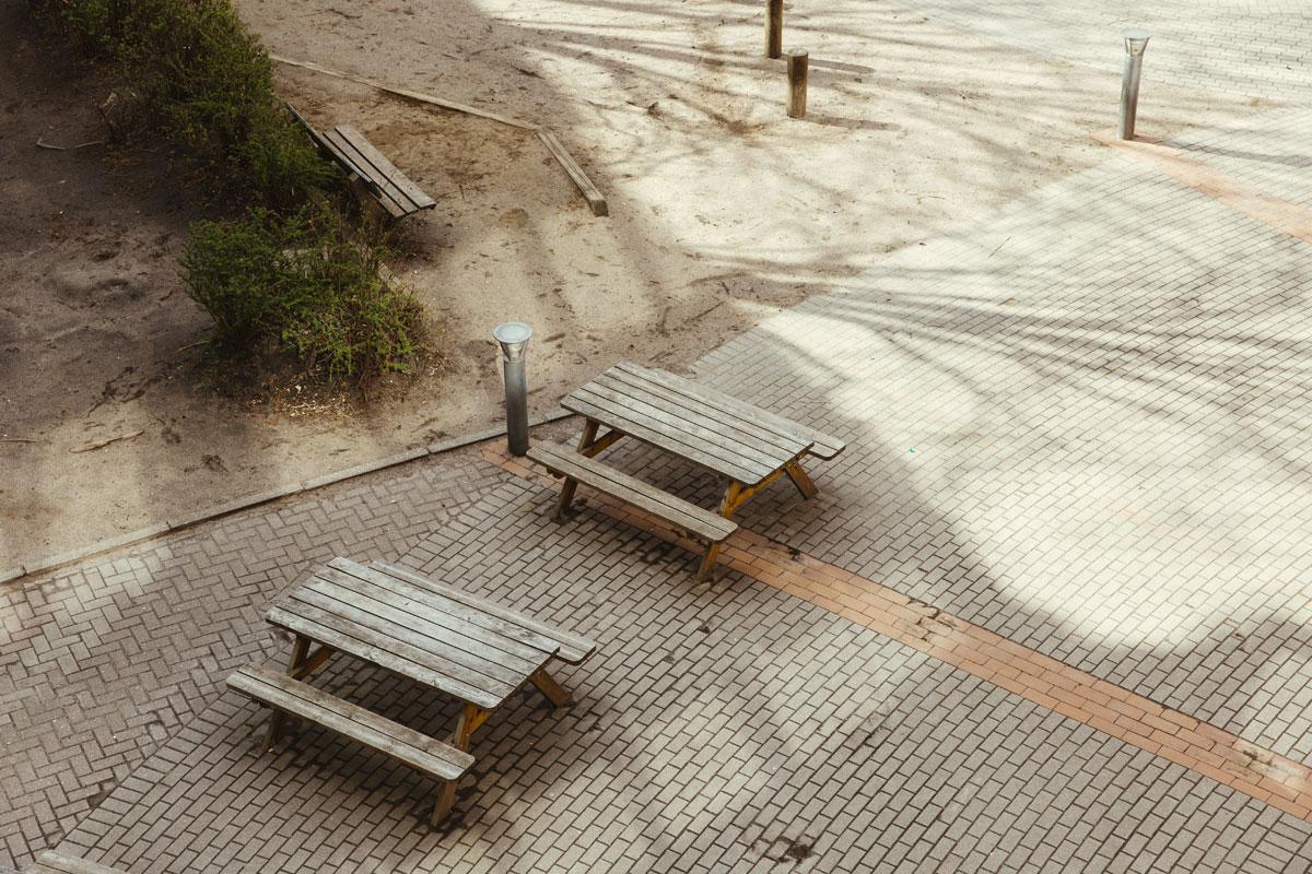 Zwei Picknickbtische mit Bänken aus Holz stehen auf dem Schulhof.