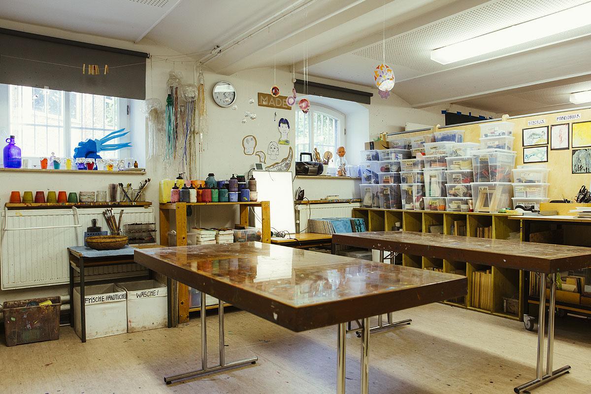 Hier sieht man den Kunstkeller der Schule mit einem großen Tisch zum Werkeln. Dahinter stehen viele regale mit Utensilien wie Wolle, Bänder, Klammern und mehr.