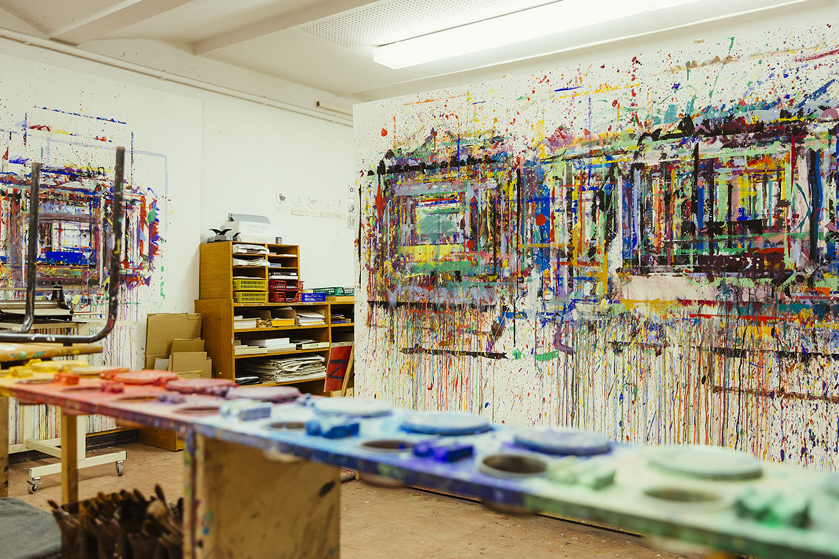 Hier sieht man den Kunstkeller der Schule mit einem Regal mit bunten Farbtöpfen. Die Wände sind ganz bunt besprenkelt vom Siebdruck.