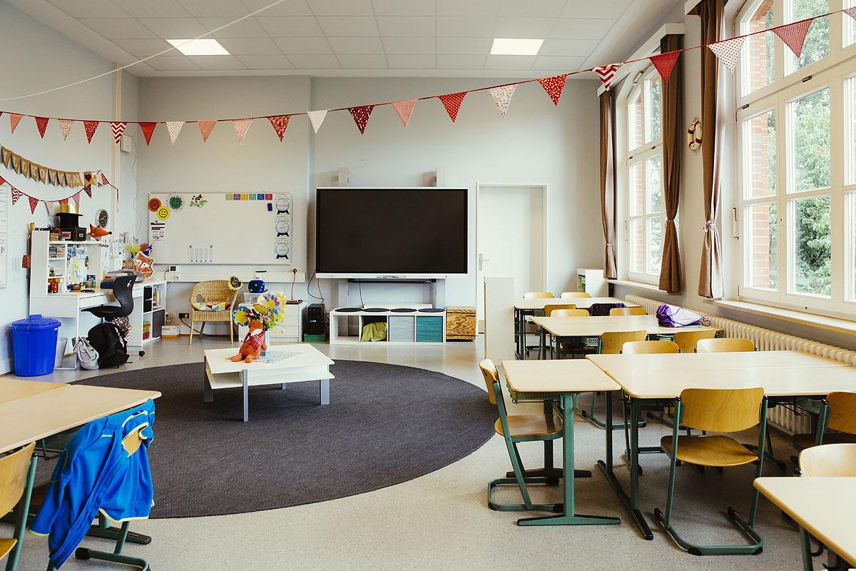 Hier sieht man eines der vielen Klassenzimmer. Ein runder grauer Teppich in der Mitte, viele holztische und Bänke, große Fenster und eine bunte Wimpelkette hängt an der Decke.