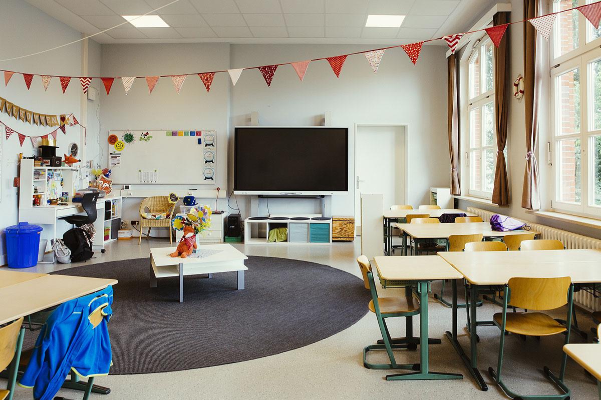 Hier sieht man eines der vielen Klassenzimmer. Ein großer Flatscreen hängt wie eine große Tafel an der Wand, viele holztische und Bänke, große Fenster und eine bunte Wimpelkette hängt an der Decke.