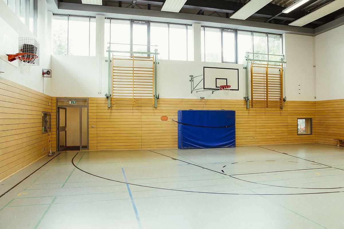 Die Turnhalle der Schule hat große Sprossen wände, die man runterziehen kann, zwei Basketballkörbe und eine große, blaue Sprungmatte die an der Wand besfestigt ist.