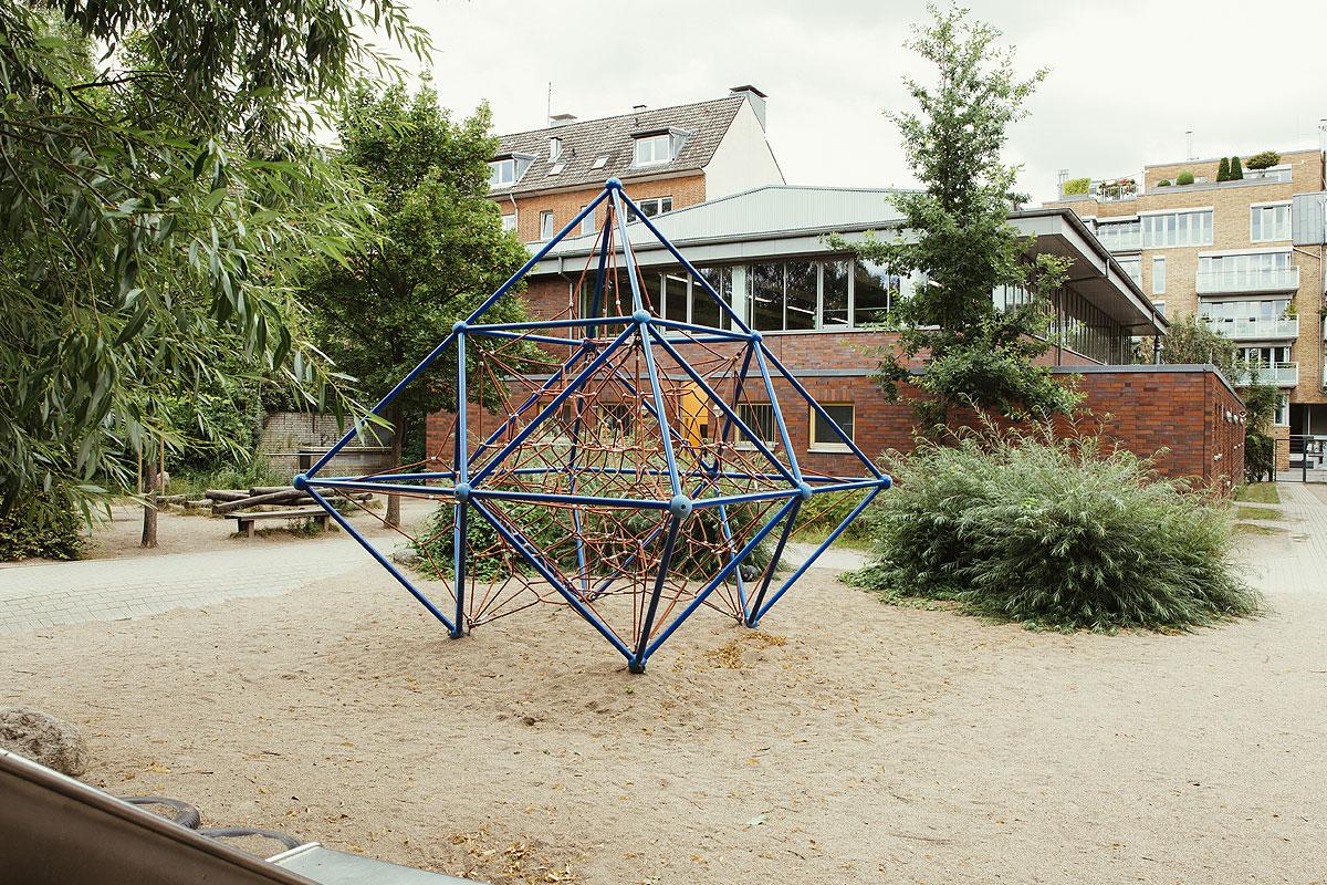Auf dem Schulhof steht ein blaues, in Sand eingebettetes Kletergerüst, welches einer Spinne ähnelt. Das Gerüst ist blau und verbunden mit einem roten Netz zum Klettern.