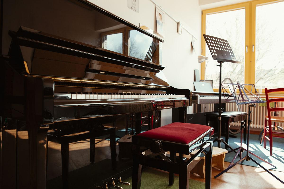 Hier siht man ein schwarzes Klavier. Davor ein Hocker mit rotem Sitzpolster. Weiter hinten steht noch ein elektronisches Klavier und ein Notenständer.