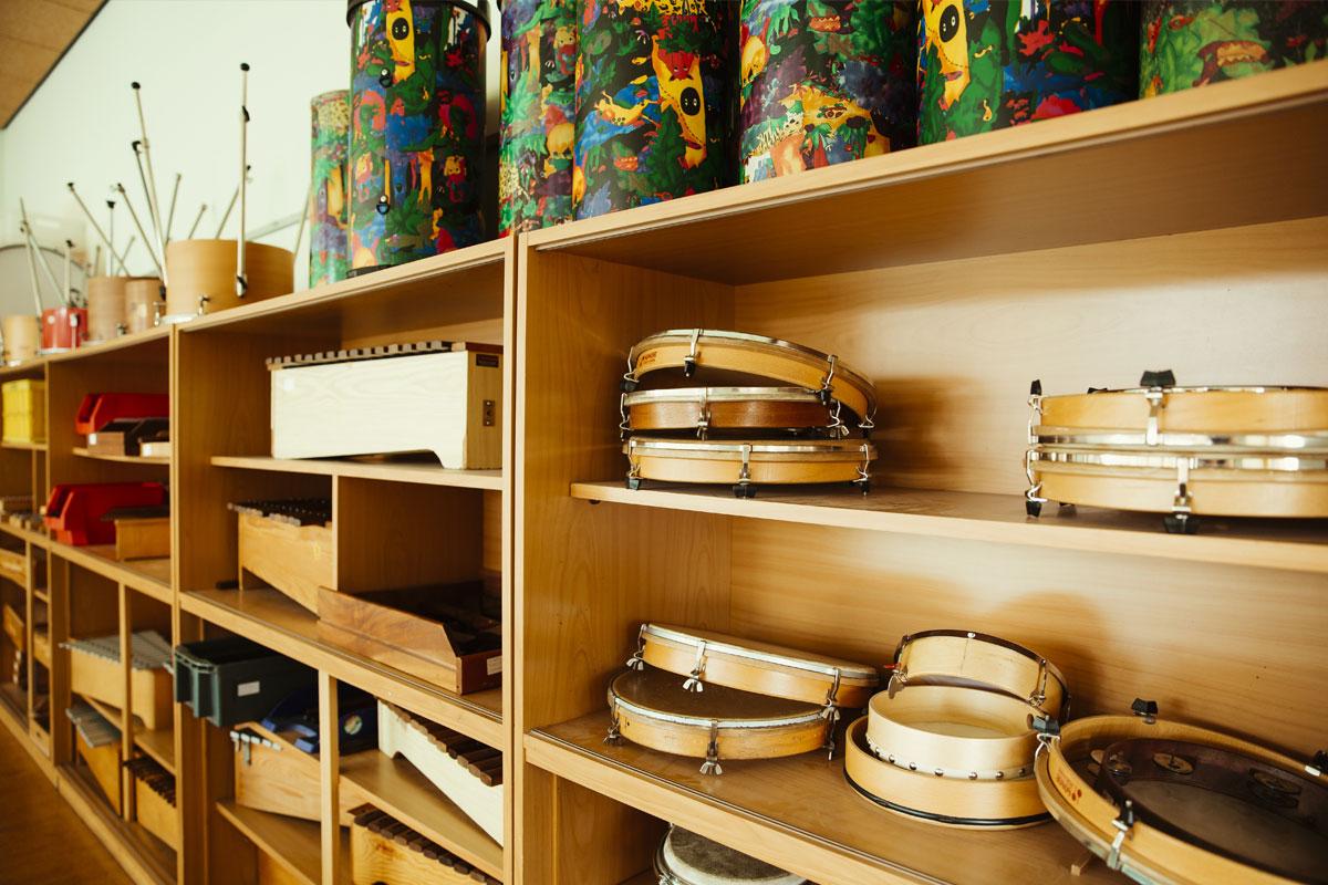 Das Bild zeigt viele Holzregale in denen sich verschiedene Instrumente befinden.