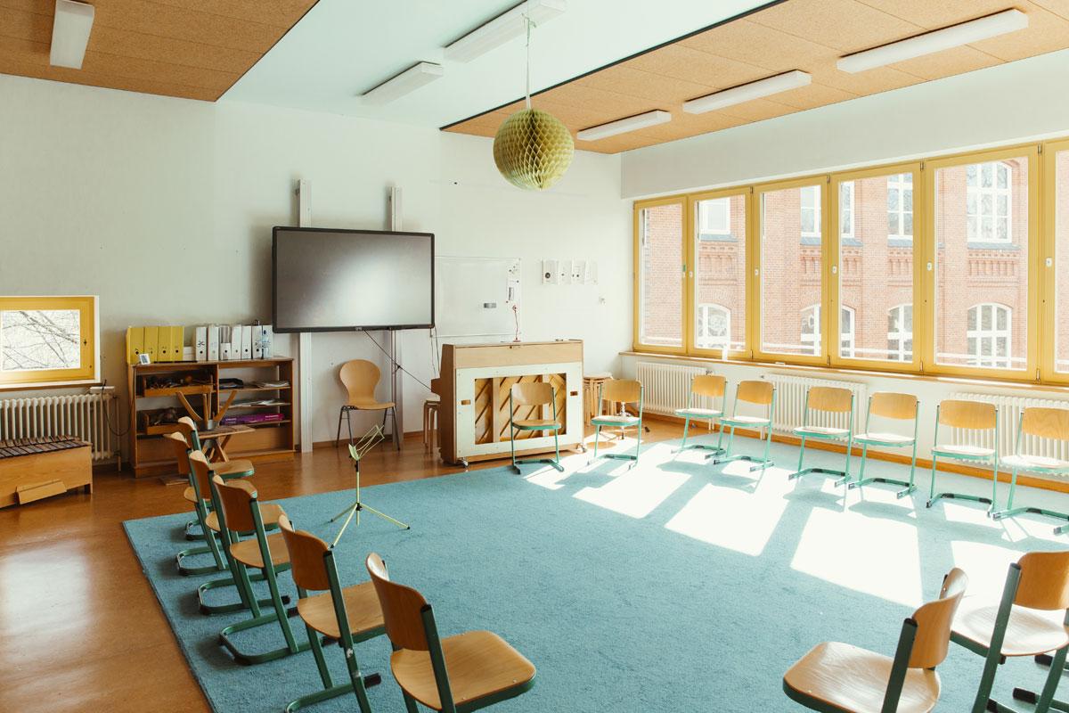 Das ist ein Musikraum in der Schule Rothestraße mit vielen Holzstühlen die in einem großen Kreis aufgestellt sind.