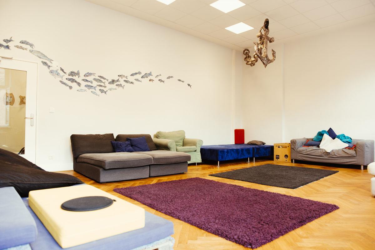 Das ist ein Blick in die Kinderwohnung der Schule. Dort stehen mehrere gemütliche Sofas und Kisssen. In der Mitte liegen Teppiche auf dem Holzfußboden.