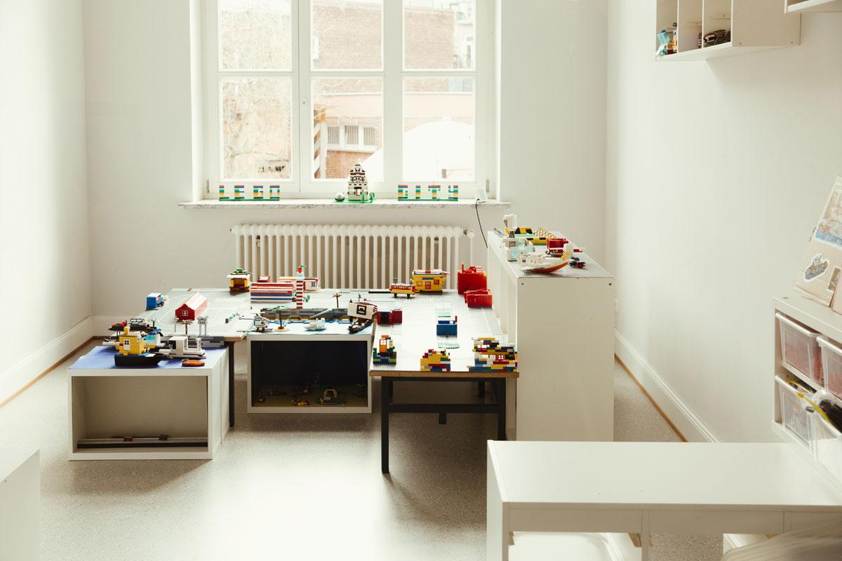 Das ist ein Blick in der Kinderwohnung der Schule. Dort steht viele niedrige Tische mit ganz vielen Legosteinen zum bauen.