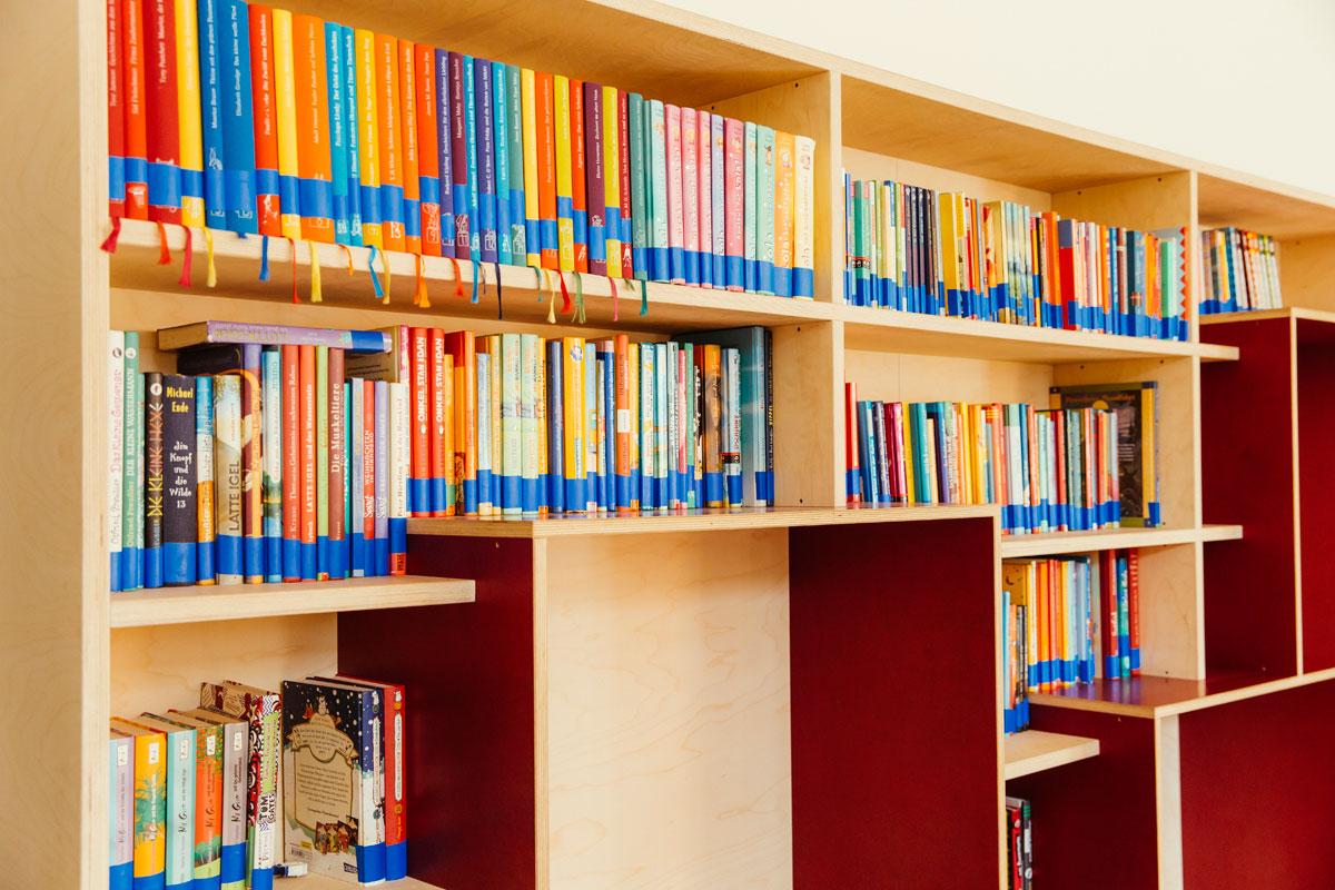 Das Bild zeigt ein großes rotes Holzbücherregal in der Bücherei. Viele Bücher sind dort rein gestellt.