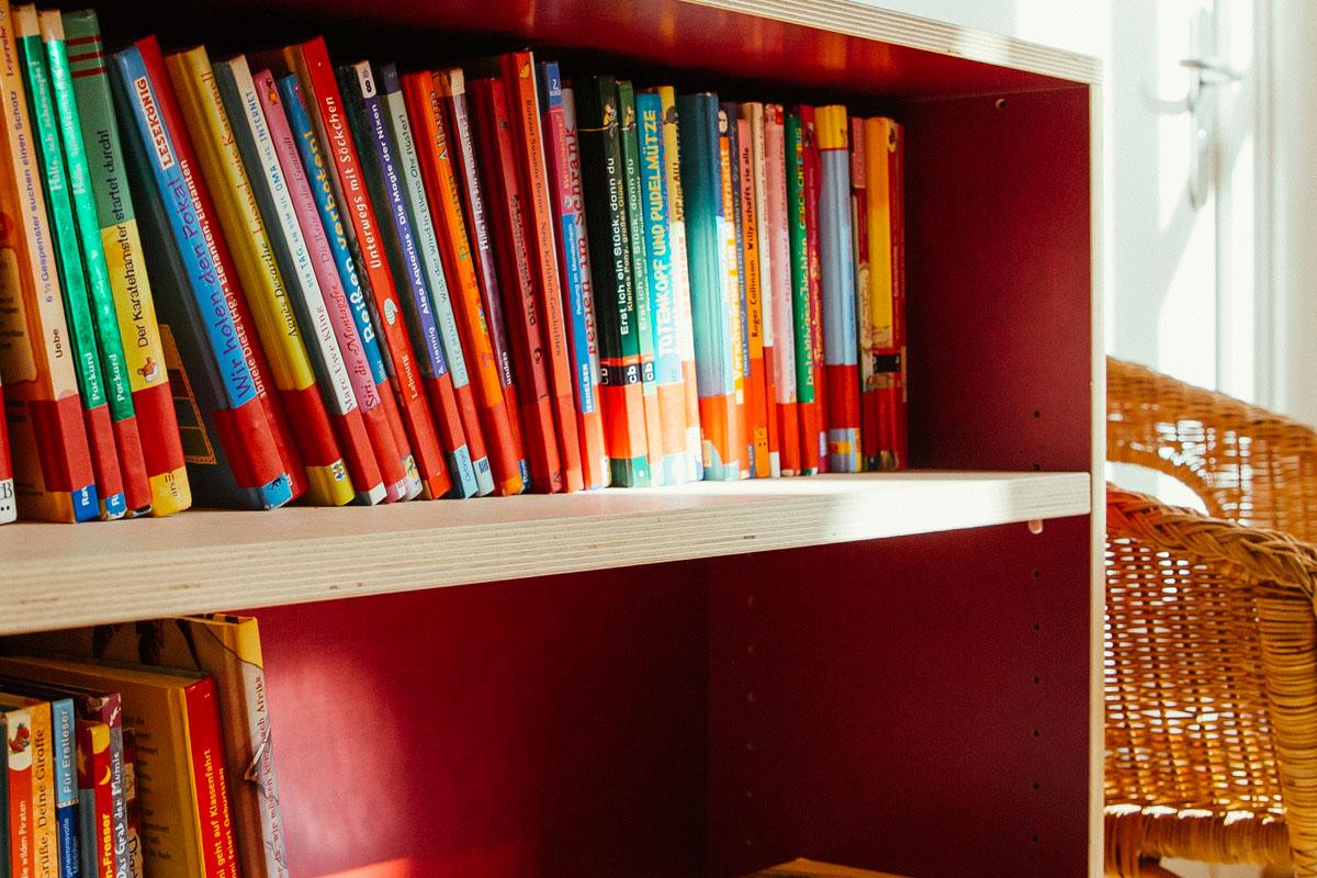 Das ist eine Nahaufnahme eines roten Holzbücherregals aus der Bücherei. Es sind dort viele Bücher zu sehen.