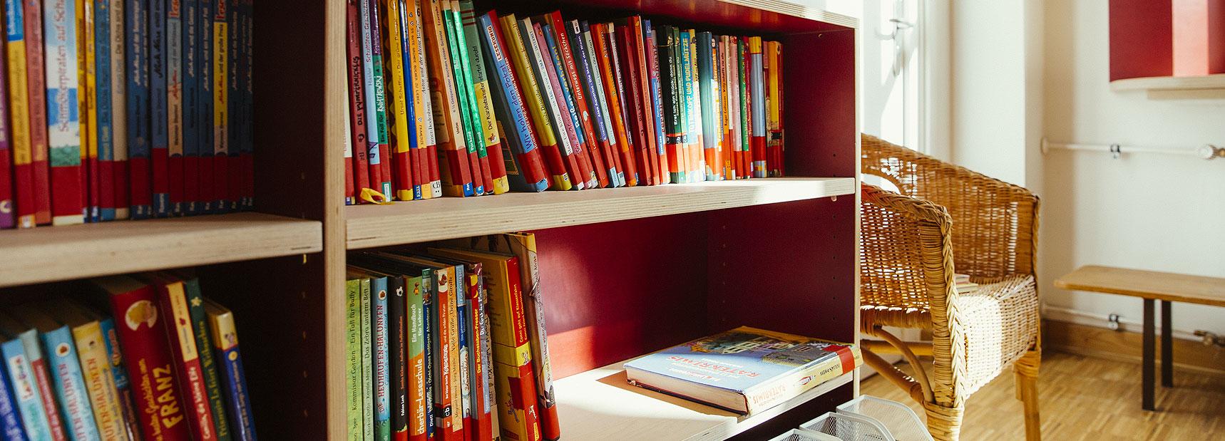 Schulbücherei mit einem roten Regal vieler Kinderbücher. Daneben steht ein Korbsessel.