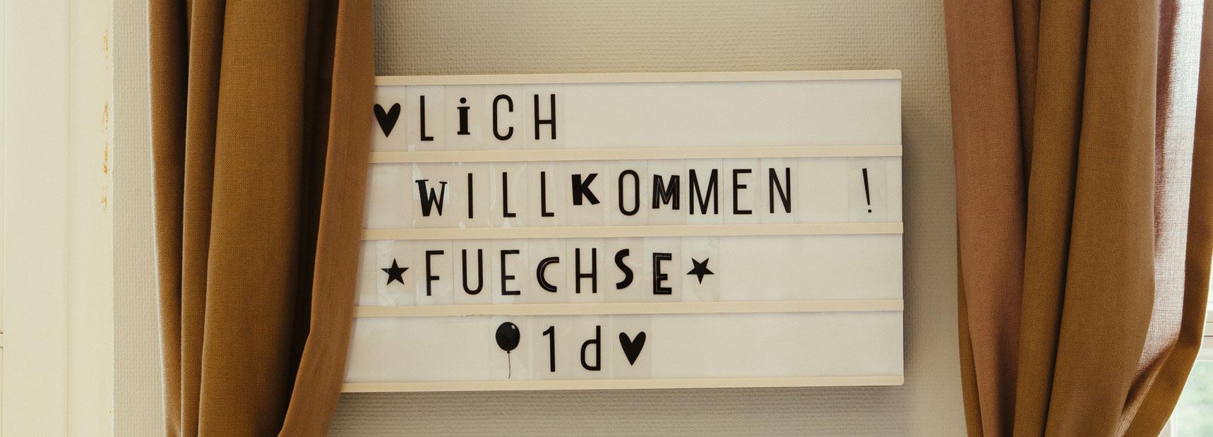 Hier ist ein Bild mit Text, welches an der Wand hängt: Herzlich Willkommen Füchse 1d