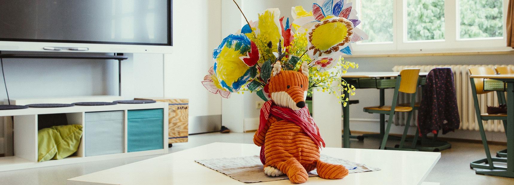 Ein kuscheliger Fuchs aus Stoff sitzt auf einem kleinen Tisch in einem Klassenzimmer und lehnt sich an eine Vase mit bunten Blumen.