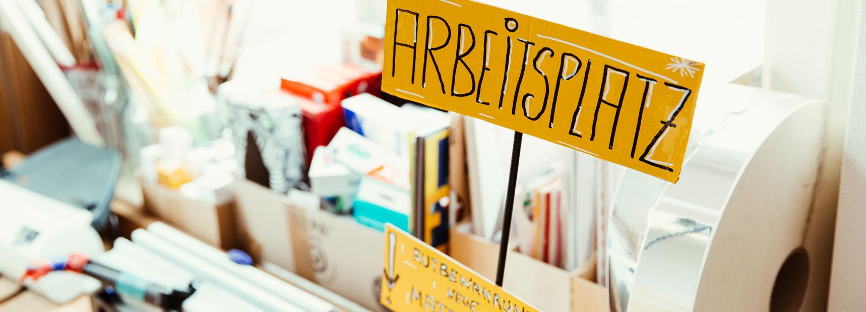 Hir sieht man einen Schreibtisch mit einem gelben Schild drauf. Darauf steht: Arbeitsplatz.