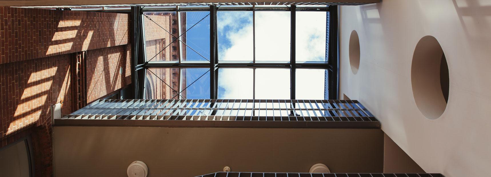 Das Treppenhaus der Schule Rothestraße von unten nach oben fotografiert. Oben sieht man durch das Glasdach den Himmel mit Wolken.