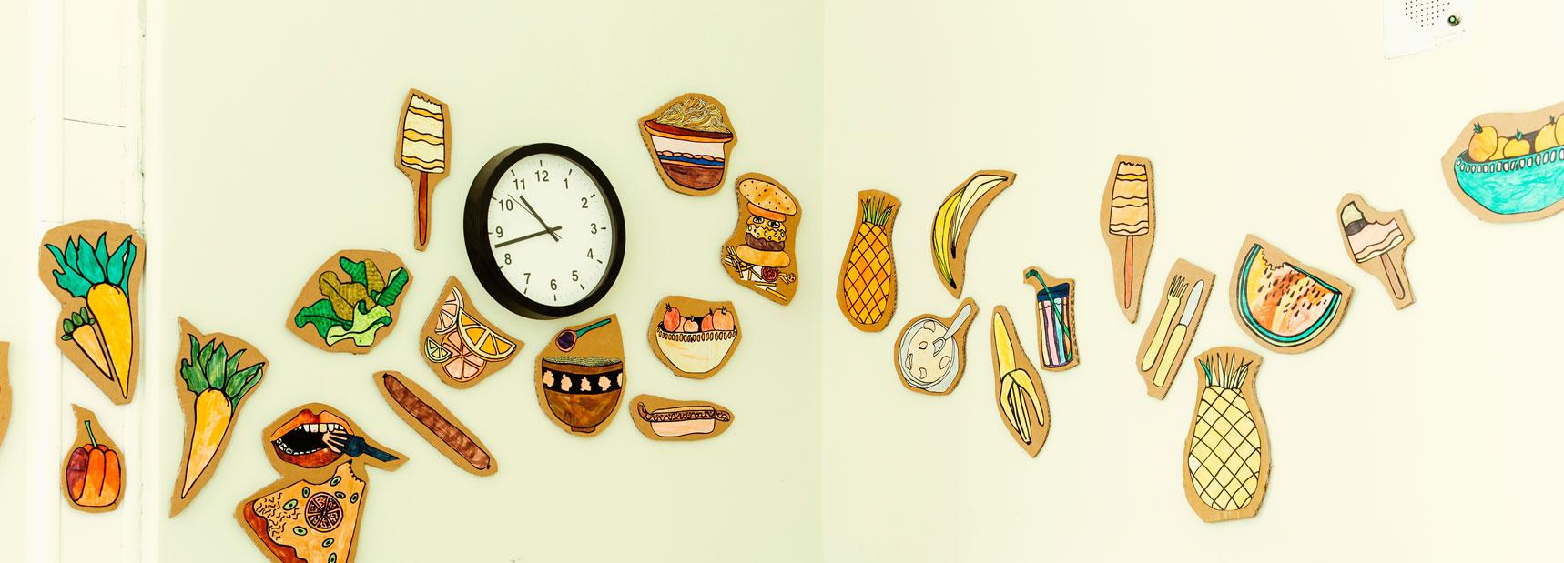 Verschiedene Grafiken die Essen abbilden wurden in der Schulmensa an die Wand geklebt und dekorieren die weiße Wand mit der Uhr.