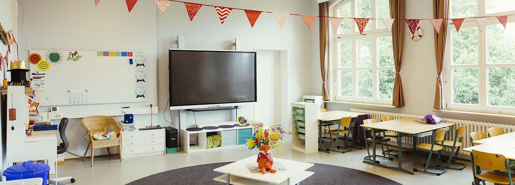 Es ist ein helles Klassenzimmer zu sehen mit großen Fenstern. Es ist ein bisschen festlich dekoriert mit einer Wimpelkette.