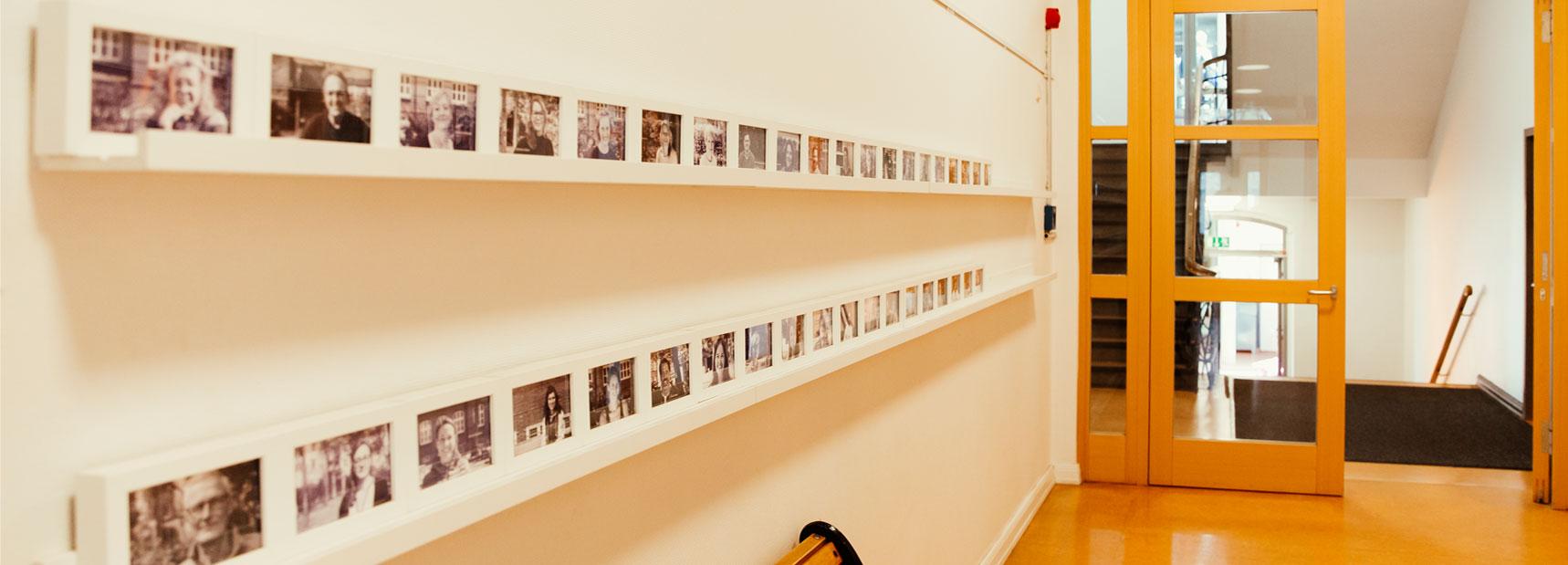 In einem der Schulflure der Schule Rothestraße wurden an der Wand lange Regale angebracht und auf diesen stehen gerahmte Schwarz/Weiß Portraits des ganzen Kollegiums.